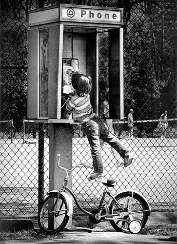 ایک موٹر سائیکل پر کھڑا ایک بچہ پے فون تک پہنچنے کی کوشش کر رہا ہے۔