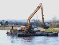 River Parrett maintenance dredging from floating platform with hopper barge and hills in background for media