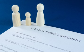 Printed child support agreement with man, woman and child wooden figures in a conceptual image for financial child support. Over blue background.