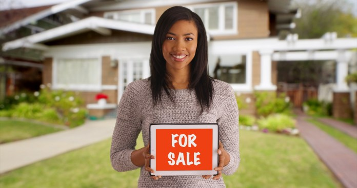 A Black woman holding a FOR SALE sign.