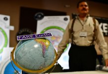 Jeffrey Diaz, right, is selling flat earth maps at his booth during Flat Earth International Conference at Crowne Plaza Denver Airport. Hundreds of people who believe the Earth is flat attended the conference.
