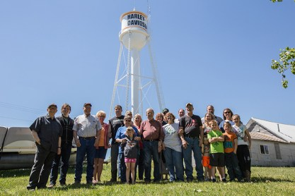 """Ryder, N.D. residents gather in front of the town's newly refurbished water tower, which has become a landmark for motorcycle riders in the Dakotas. To launch riding season, Harley-Davidson will ride into Ryder Saturday, June 3 with the aim of creating the first fully motorcycle licensed town. To commemorate the experience, Ryder city officials will change the town's name to """"Riders"""" this riding season."""