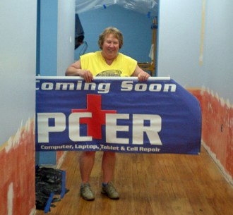 InterMedia3 owner Maggie Wannemacher holds the PC-ER sign that will be going up soon at a later retail establishment north of Van Wert. (photo submitted)