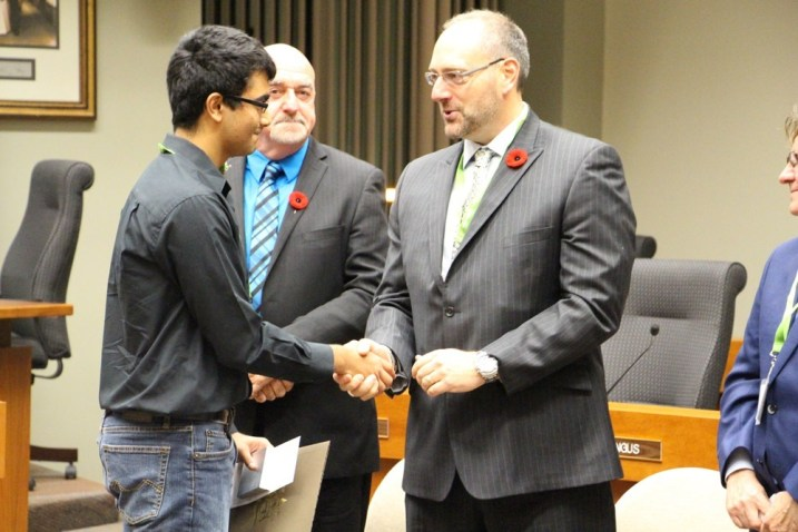 Jeevan Chahal, left, shakes hands with Andrew Covello of Thunder Bay Hydro, event sponsor, after being presented with the Young Leader Award at the 2014 Mayor's Community Safety Awards Ceremony.