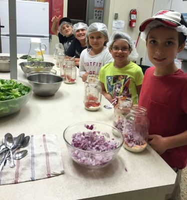 Fun in a community kitchen: Kristen Pouru and Seok Koon Chin from Our Kids Count help Marley and Garon prep and cook a healthy meal. In the last six months, 178 different kitchen programs have supported children and adults while they learn the skills and joys of cooking.
