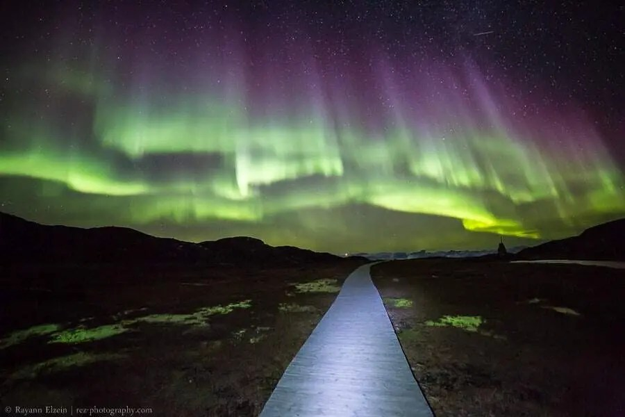 Aurora borealis above the boardwalks of the Unesco Ilulissat Icefjord in Greenland