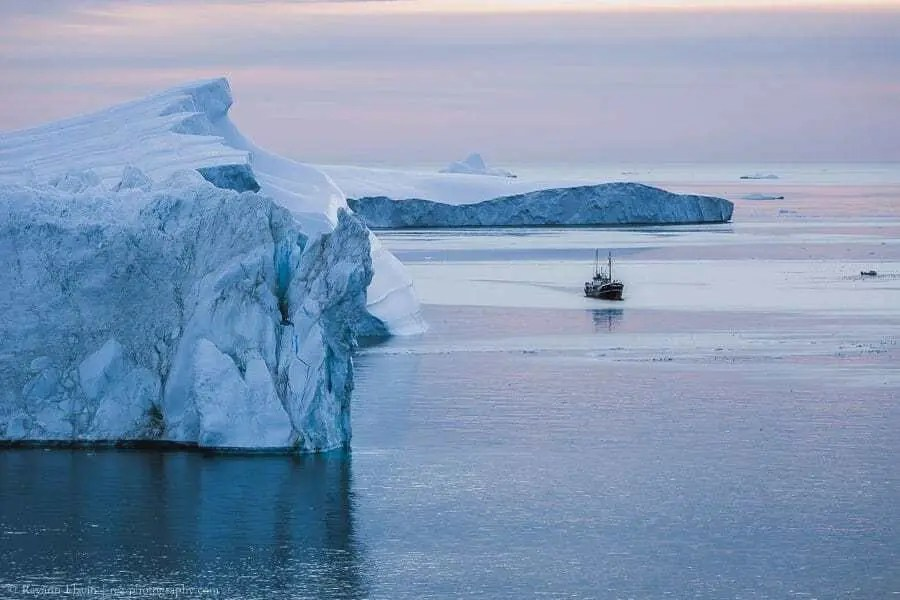 Boat and icebergs in the UNESCO Ilulissat Icefjord in Greenland