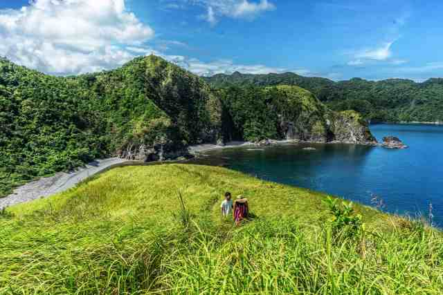 two people hike to top of Lantangan beach in the caramoan islands on island hopping day tour in philippines. mountains and water are in background