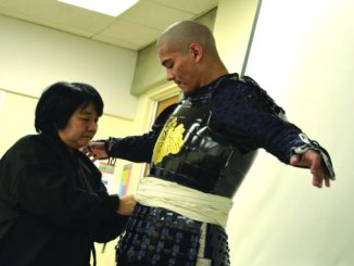 Student volunteer demonstrating samurai armor.