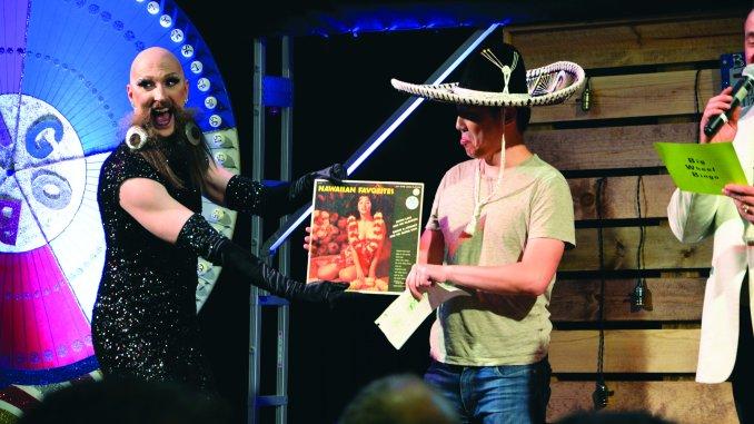 Waxie Moon presenting an award to a bingo winnner.
