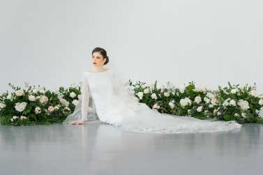 fresh look design bride lounging in front of lush greenery with white flowers