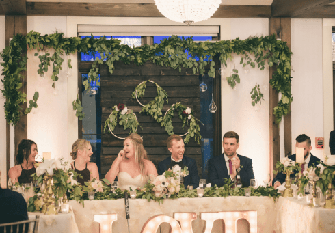 fresh look design wedding head table with green wreaths and green draping