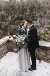 fresh look design bride and groom kissing in the snow with groom holding the brides large bouquet