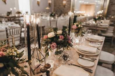 fresh look design long wedding tables with tall candles, pink and white flowers, blush and white place settings
