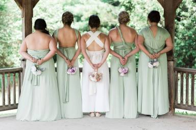 BridesMade bride with her bridesmaids dressed in long pale green bridesmaid dresses