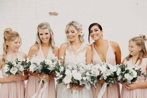 BridesMade bride with her bridesmaids in blush bridesmaid dresses and white and green bouquets