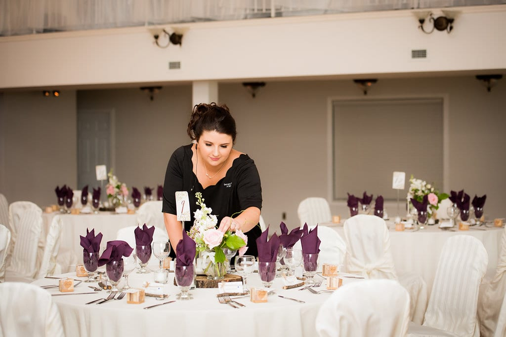 servers with a smile owner Rebecca placing centrepieces