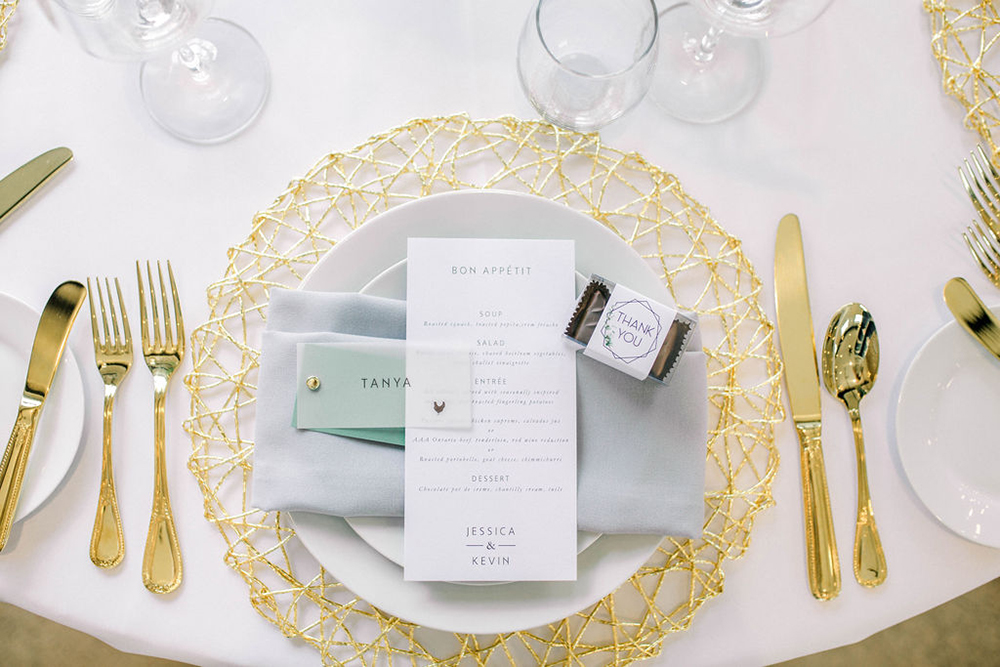 a clean white bon apetit menu card ontop of a gold wire plate charger