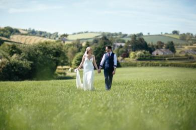 creme couture bride and groom walking in the grass