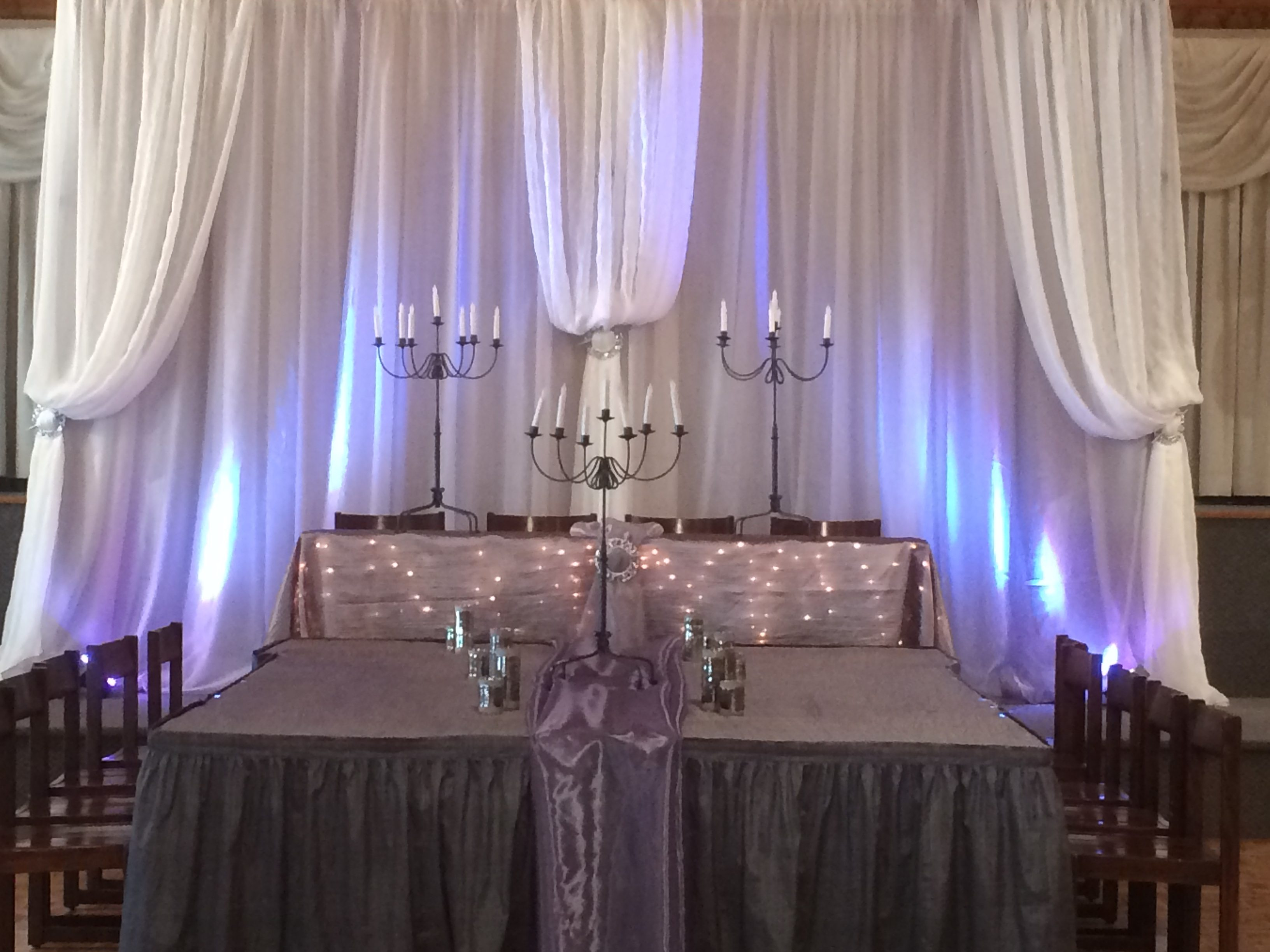 Now & Always head table with white draped backdrop, uplighting and candelabras