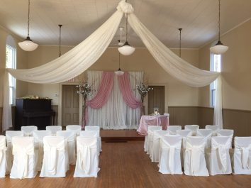 Now & Always pink and white wedding ceremony backdrop with white guest chair covers and white ceiling drape