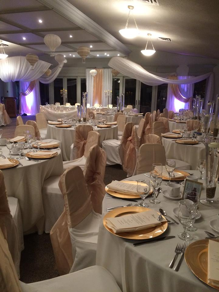 Now & Always white and gold guest tables with gold charger plates and chair sashes