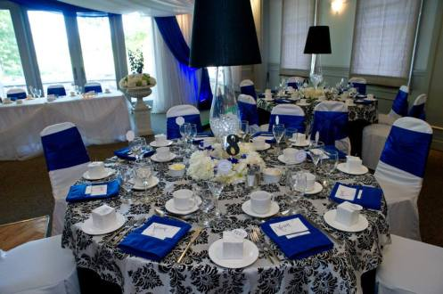 Now & Always black and white damask table linens with pops of royal blue on wedding guest tables
