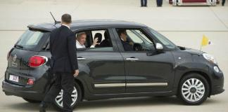 Pope Francis waves as a passenger in a Fiat 500L.