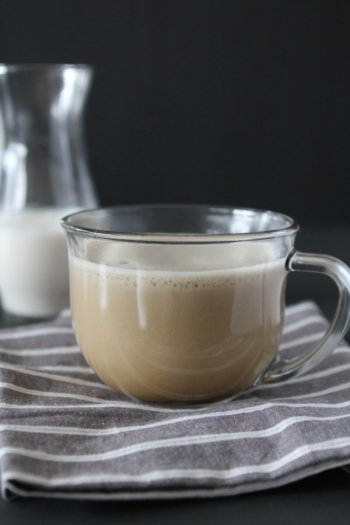 side view of a whole30 almond milk latte with milk froth on top