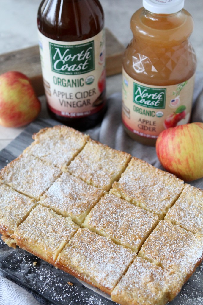 overhead shot of healthy Gluten-Free Apple Bars cut into squares with apple cider and apple cider vinegar in the background