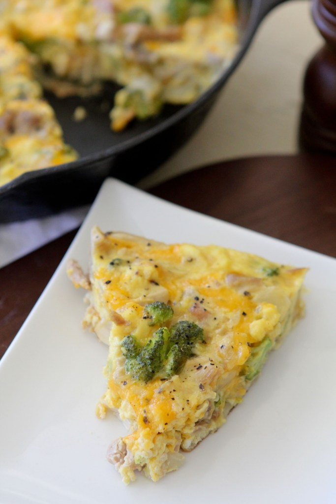 a slice of broccoli chicken and cheddar frittata on a white plate with a black skillet in the background