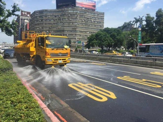 A road sprinkler cools the asphalt in Taipei City