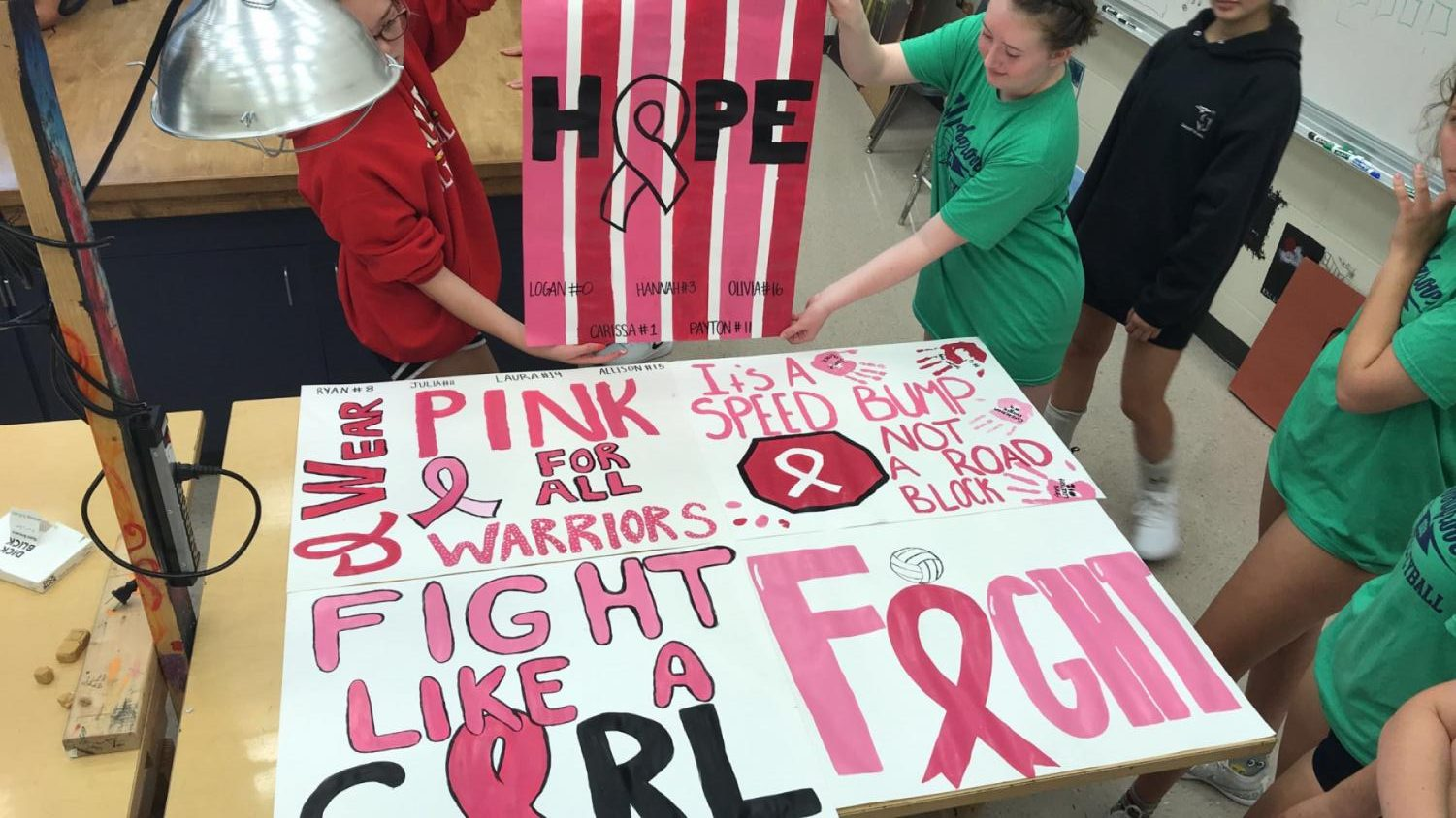 Woodgrove volleyball players get together to create posters for their annual Dig Pink game against Loudoun Valley.