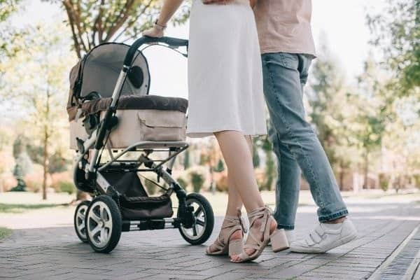 Couple walking in park with baby stroller.