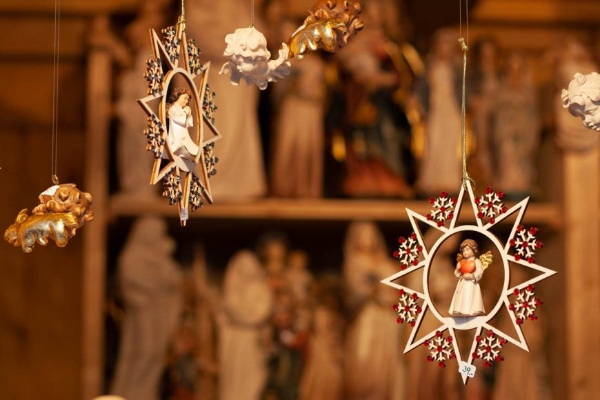 Two hanging decorations in the shape of stars, decorated with red snowflakes, with angles praying inside them.