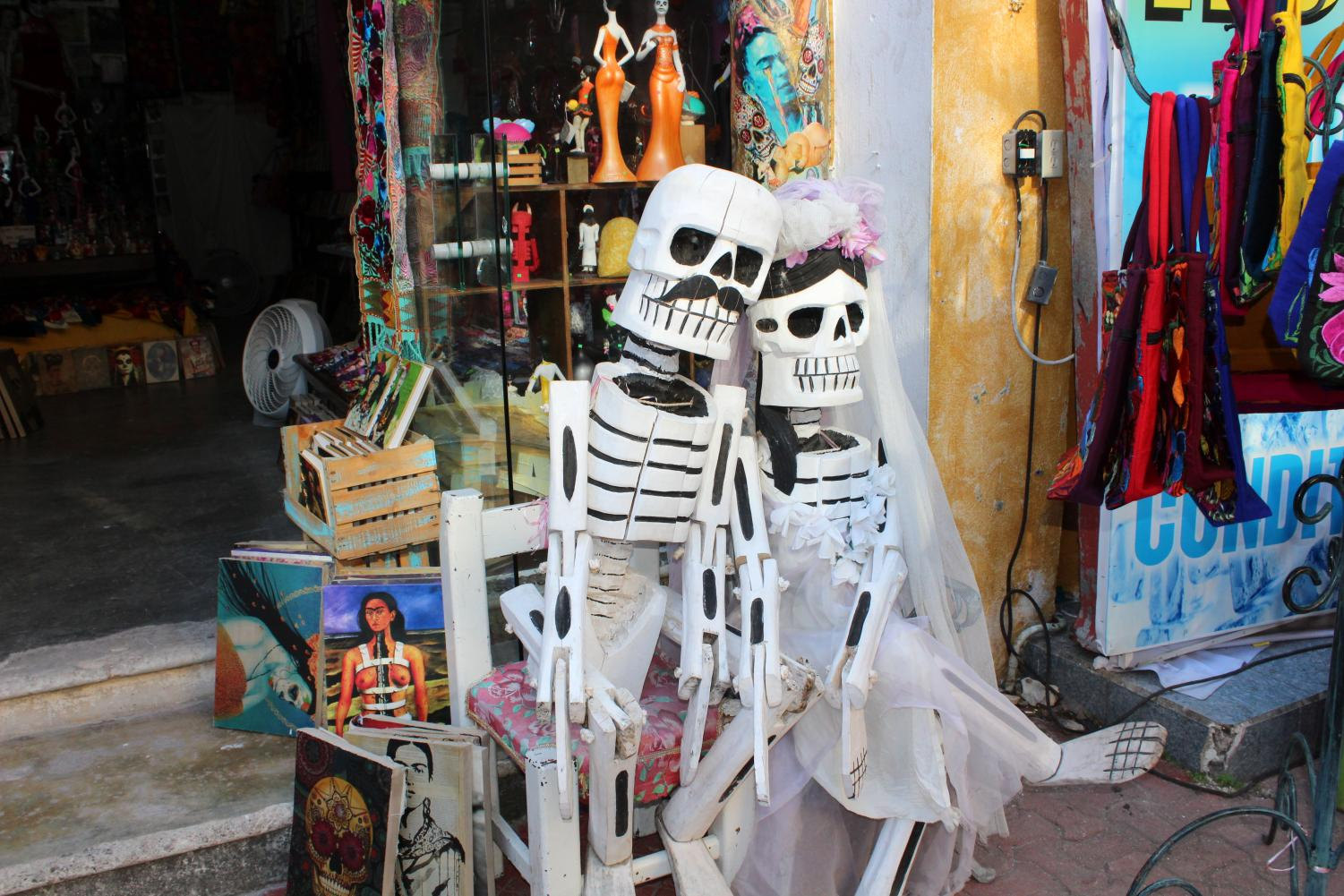 A statue outside of a shop in Playa De Carmen, Mexico surrounded by Frida Kahlo artwork for sale.