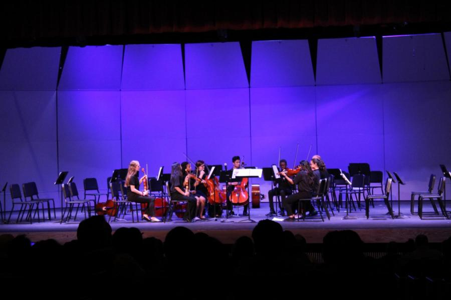 Orchestra+students+preforming+a+piece+for+their+first+concert.+