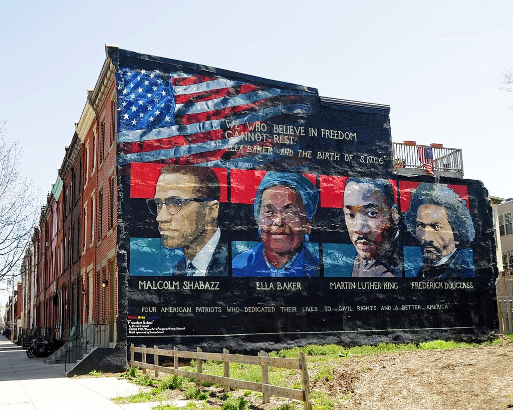 Mural on the wall of row houses in Philadelphia. The artist is Parris Stancell, sponsored by the Freedom School Mural Arts Program. Left to right; Malcolm Shabazz (Malcolm X), Ella Baker, Martin Luther King, Frederick Douglass. The quote above the pictures,