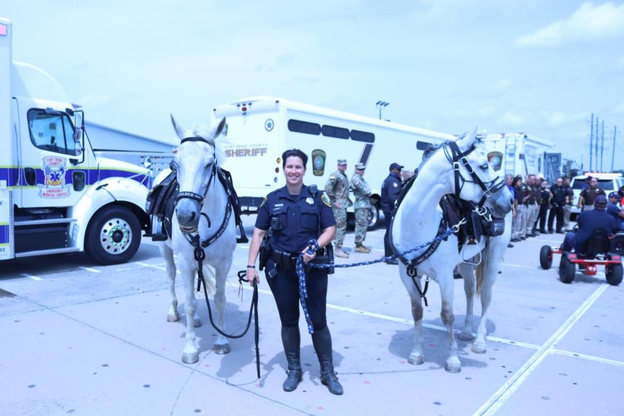 The+female+officer+and+the+two+horses+posing+amidst+the+crowd.+