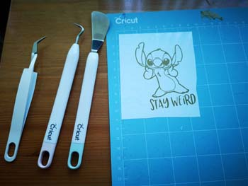 Cricut tools with gold vinyl cut of stitch with words saying stay werid on a blue mat