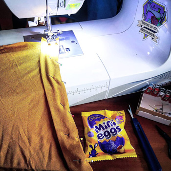 Sewing Machine With Yellow Viscose Jersey With Neckband Pinned In Place, Packet of Mini Eggs, Seam Ripper And Box Of Pins.