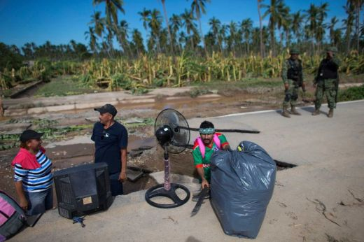 Banana plantation workers with their belongings, standing in a section of missing roadway (timesunion.com)