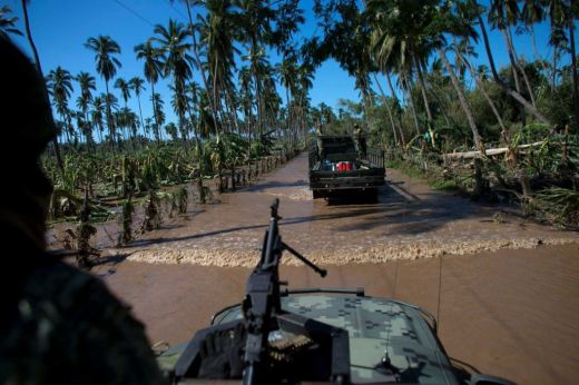 Army trucks drive through receding floodwaters amidst devastated banana plantations, as they try to reach the village of Rebalse (timesunion.com)