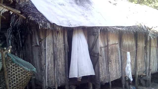 maison avec le toit renforcé par le plastique d'un gros sac d'aide de l'ONU