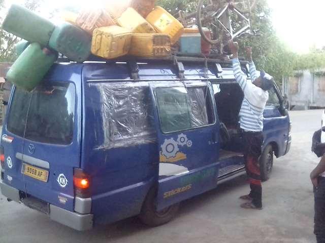 Taxi-brousse bleu avec plein de bidons sur le toit