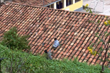 A boy and his mother working to repair a tile roof.