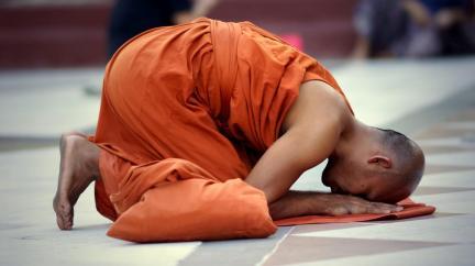 Buddhist monk saving prayers at the Schwedagon Pagoda in Yangon, Myanmar.