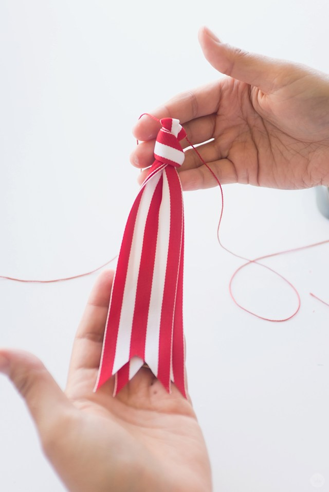 Red and white ribbon tied on red cord.