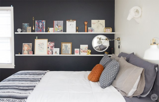 Tips for displaying art: two pictures ledges on a wall beside a bed display framed art, collectibles, record album, and a mirror
