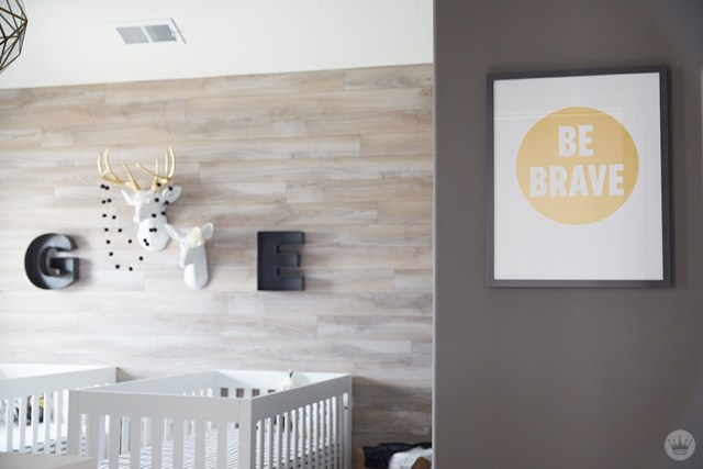 "Tips for displaying art: A nursery features initial letters G and E displayed with ceramic deer busts; an accect wall features a framed print with the words ""BE BRAVE"""